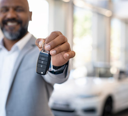 Smiling salesman holding new car keys in car showroom. Businessman is suit showroom showing car keys. Closeup hands of african man holding keys on car rental salon with copy space.